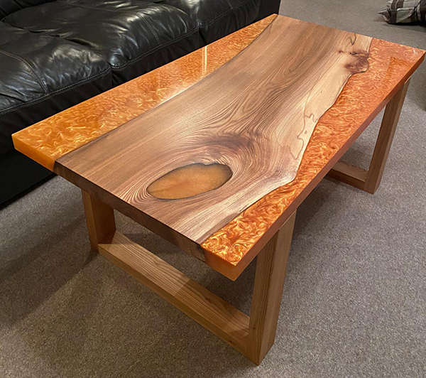 Stunning Elm wood table with magic orange pigment used in the resin